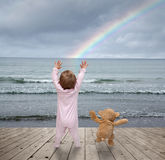 Baby game 15. Small child and a teddy bear watching rainbows Royalty Free Stock Photo