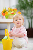 Baby gathering Easter eggs in basket Royalty Free Stock Photography