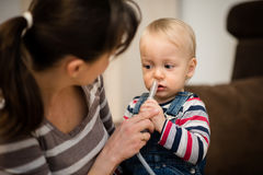 Baby-Gebrauchsnasensonde der Mutter helfende lizenzfreies stockbild