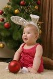 Baby gegen Weihnachtsbaum Stockfoto