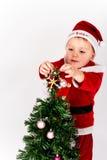 Baby gekleidet als Santa Claus, die den Stern auf die Oberseite von C setzt stockfotografie