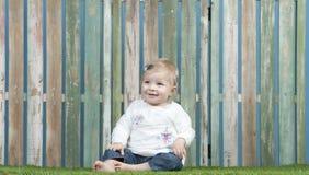 Baby gesetzt auf Gras vor einem Zaun Stockfotografie