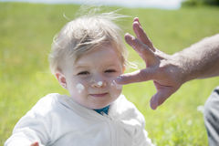 Baby getting suncream on her face Royalty Free Stock Image