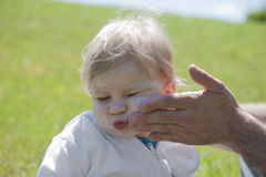 Baby getting suncream on her face Royalty Free Stock Photography