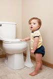Baby getting into toilet paper. Baby getting caught getting into toilet paper Stock Image