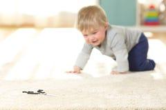 Baby in gevaar die naar een schaar kruipen stock foto