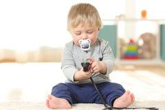 Baby in gevaar het spelen met een elektrische stop royalty-vrije stock fotografie