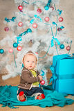 A baby with gifts at Christmas tree Stock Image