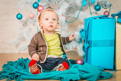 A baby with gifts at Christmas tree Stock Photography