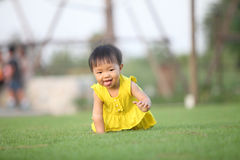 Baby gir crawl on lawn in the park ,facetious Stock Photos