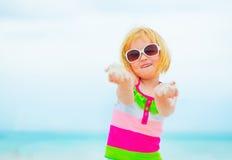 Baby gir, das Sand bei der Stellung auf Strand zeigt lizenzfreies stockbild