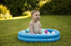 Baby gir splashing in a paddling pool. In summer Royalty Free Stock Photo