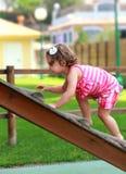 Baby giri climbing up on wooden Stock Image