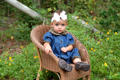 Baby Girl. A darling baby girl sitting in a wicker chair wearing denim trimmed in leopard with a big bow in her hair outdoors Royalty Free Stock Photography