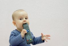 Baby girl. Curious baby girl chewing tv remote control and looking at camera Stock Photo