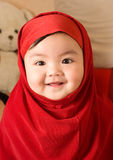 Baby girl. A baby girl wearing a red muslim dress Stock Photo