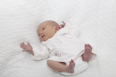 Baby girl. A newborn baby girl resting on a white blanket royalty free stock photos