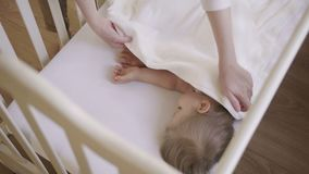 Free Baby Girl 2 Years Old Sleeping In A Crib Covered White Blanket. Mom Covers The Baby With A Blanket. Daytime Sleep Stock Photo - 118080790