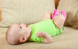 Baby girl. Portrait of cute little baby girl on sofa Royalty Free Stock Photos