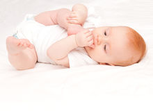 Baby Girl. Cute Baby Girl Sucking Her Toes on White Background Stock Photo