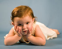 Baby Girl. A cute baby girl lying down with head in hands stock image