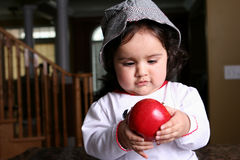 Baby girl. Sweet and cute baby girl eating apple Stock Photography
