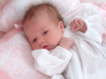 Baby Girl. Newborn baby girl on pink and comforter and pillows Stock Images