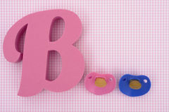 Baby Girl. Letter B with pacifiers on pink background royalty free stock photos