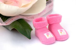 Baby girl. Pink newborn socks with ribbon and magnolia flower Stock Photos