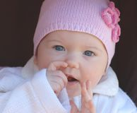 Baby girl. Portrait of beautiful baby in rose hat Stock Image