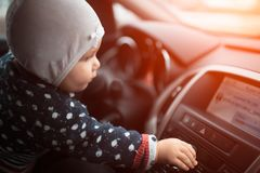 Baby girl adjusts the volume control of car audio system.  royalty free stock image
