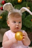Baby girl  against Christmas tree with funny ears Royalty Free Stock Photography