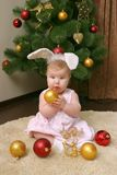 Baby girl against Christmas tree with funny ears stock photography