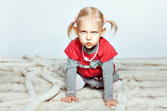Baby girl is on all fours. Baby blonde girl is on all fours and grimaces Stock Photo