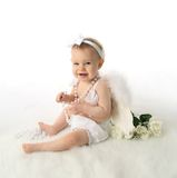 Baby girl angel. Soft portrait of a baby girl wearing white angel wings and white pearl necklace Stock Photos