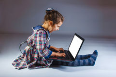 Baby girl angry shouts sits playing laptop on gray Royalty Free Stock Photography