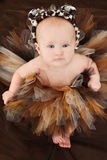 Baby Girl in Animal TuTu. Adorable 4 month old baby girl in animal print tutu and hat over brown Stock Photo