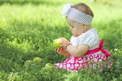 Baby girl with apples in the garden Royalty Free Stock Photos