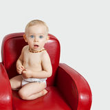 Baby girl on an armchair.bis Royalty Free Stock Photos