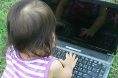 Baby girl asian play computer Stock Photos
