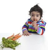 Baby Girl Attempting to Eat Carrot Royalty Free Stock Photos