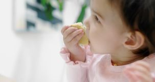 Baby girl attemtping to eat a cookie by herself. Cinematic 4K footage. Real life, not staged stock video footage