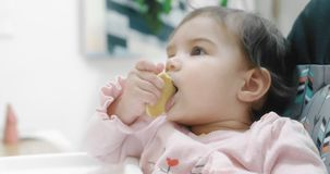Baby girl attemtping to eat a cookie by herself. Cinematic 4K footage. Real life, not staged stock footage