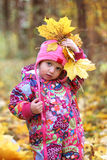 Baby girl in autumn maple leaves Royalty Free Stock Photos