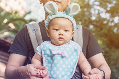Baby girl in a baby carrier with father Stock Images