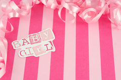 Baby girl background. Pink baby girl background with stripes and pink curled celebratory ribbon Stock Photography