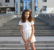 Baby girl on a background of a modern building. Soft focus bokeh Royalty Free Stock Photos