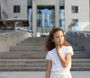 Baby girl on a background of a modern building. Soft focus bokeh Stock Image