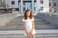Baby girl on a background of a modern building Stock Photos