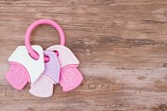 Baby Girl Background. A pink and white teething ring on weathered wood with copy space for your message Stock Images